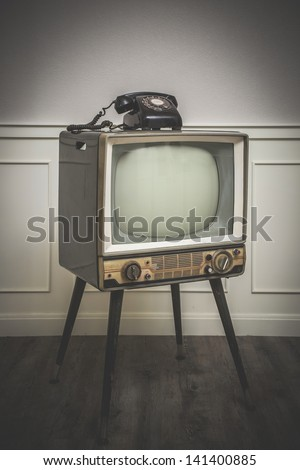Old Television with 4 legs in the corner of vintage room and a black old telephone on it, edited with vintage old style with vignette