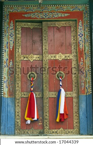 Old temple door decorated with tassels at Thikse Buddhist monastery. Ladakh, India - stock photo