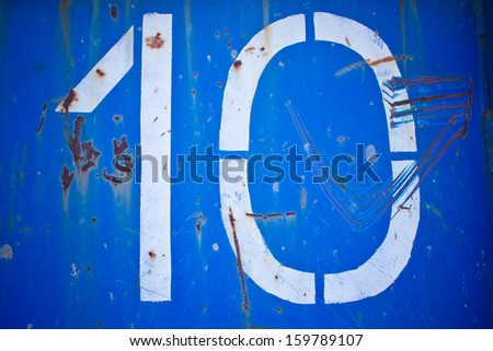 Old ten number on rusty blue metal texture