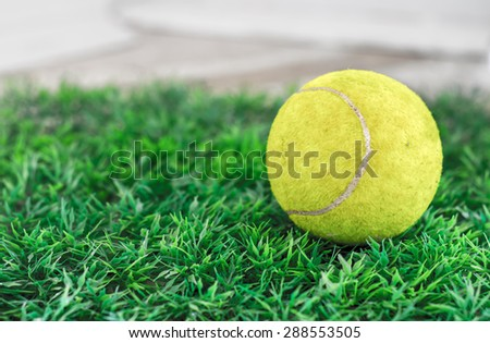 old tennis ball on grass - stock photo