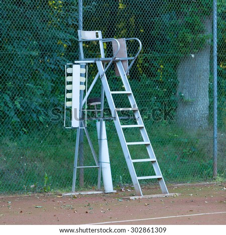 Old tennis umpire chair on a red tennis court - stock photo