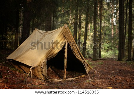 old tent in the autumn forest, home for adventure and travel - stock photo