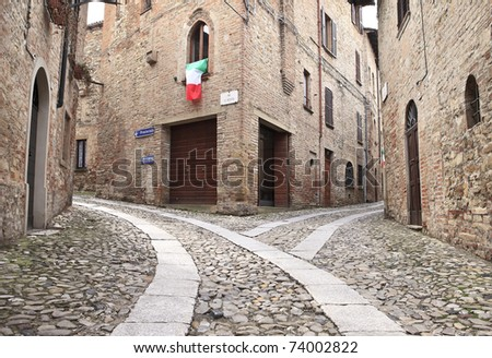 Old terraced houses on cobbled alleyway, Castell'Arquato, Italy - stock photo