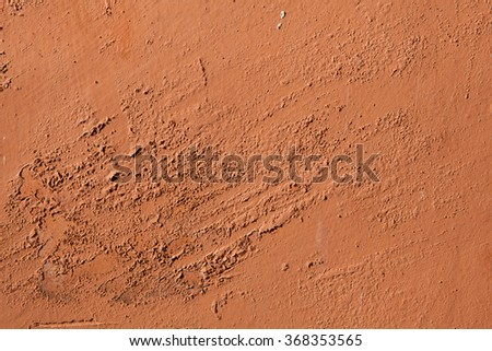 Old terracotta painted stucco wall with chipped paint. Background texture. - stock photo