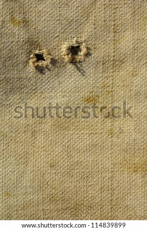 old textured canvas background. worn tattered fabric with holes - stock photo