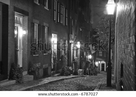 old 19th Century cobble stone road in Boston Massachusetts, lit only by the gas lamps revealing the shuttered windows and brightly lit doorways of the rowhouses on Acorn Street - stock photo