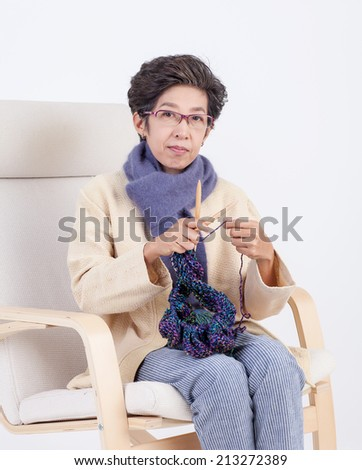 Old Thai woman knitting on the chair and waiting her daughter  - stock photo
