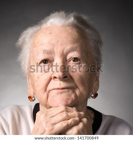 Old  thoughtful woman on a gray background - stock photo