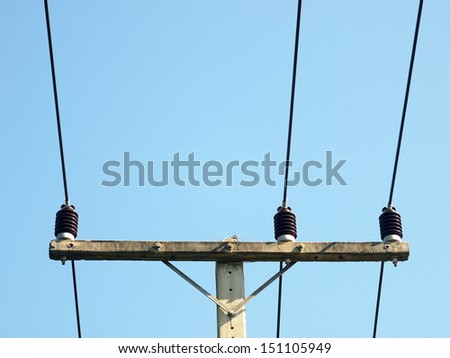 old three-phase power electricity line installed on top of a pylon with ceramic isolators blue sky background
