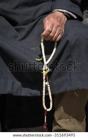 Old Tibetan woman holding buddhist rosary in Hemis monastery,  Ladakh, India. Hand and rosary, close up - stock photo