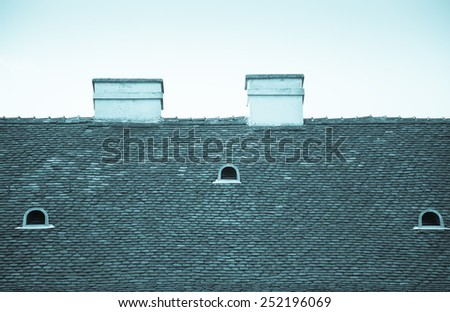 Old tiled roof with chimneys and dormers on blue sky background. Toned. - stock photo