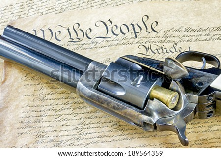 Old time revolver with the constitution - stock photo