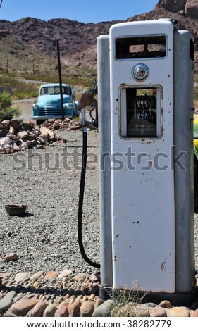 old time vintage gas pump in the middle of no-where with mountain view and a beatup old truck