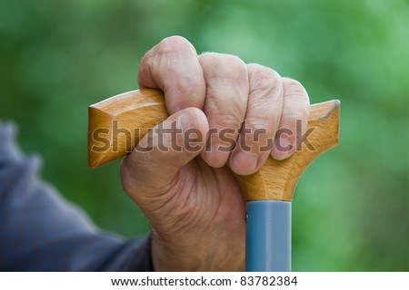 Old tired man's hand holding stick on a green background - stock photo