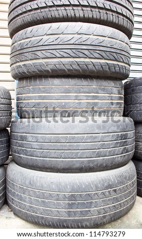 old tires stack in front of garage - stock photo