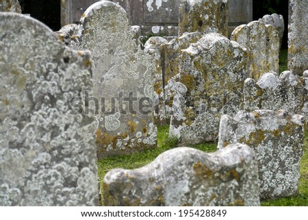 Old tomb stones; jumble of lichen-covered tombstones in cemetery  - stock photo