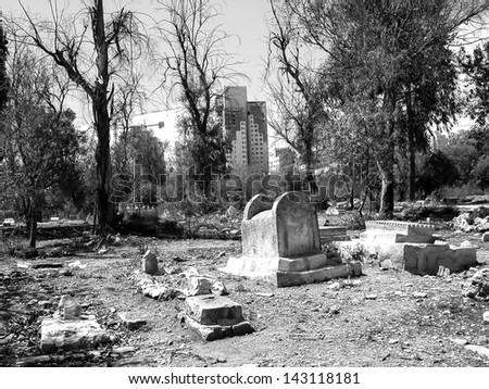 Old tombs in muslim cemetery and modern skyscrapers at background. Jerusalem. Black and white. - stock photo