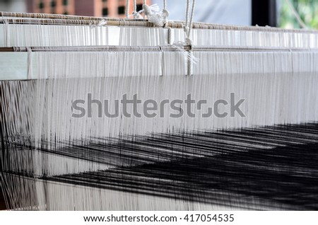 Old tool to make the thread bobbin for the shuttle of ancient loom and Cotton is raw for weave, tools to work natural textile fiber.Yarn warping machine in a textile weaving  - stock photo