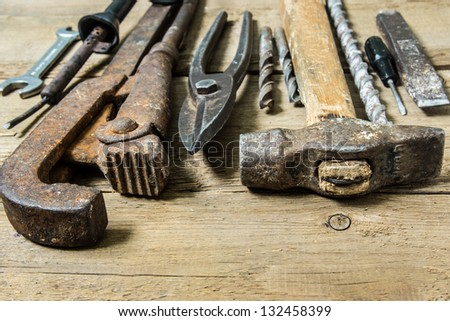 Old tools (hammer, drills, wrench, scissors for metal)  on wooden background - stock photo