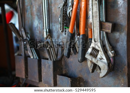 Old tools hanging on metal wall in workshop