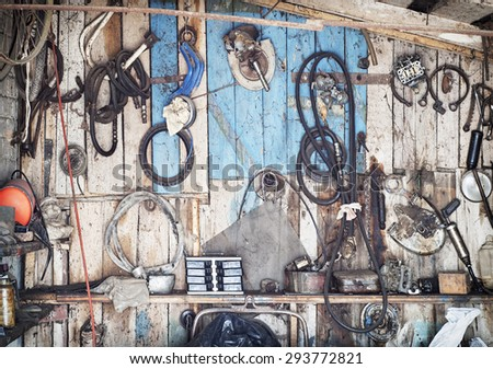 old tools hanging on wooden wall in a tool shed - stock photo