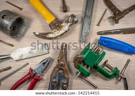 Old tools on wooden background.