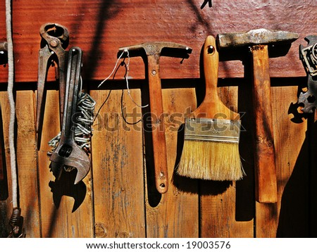 old tools, paint brush & hammers on wooden wall - stock photo