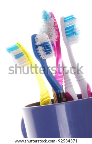 old toothbrushes in a blue glass on white background - stock photo