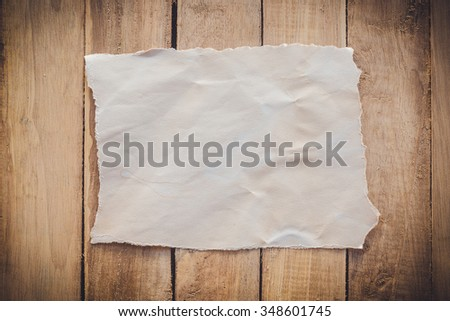old torn paper on wood background with space
