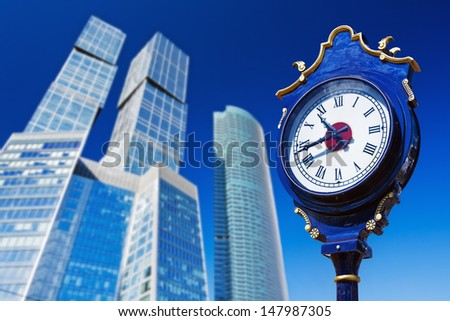 old town clock on the background of modern skyscrapers - stock photo