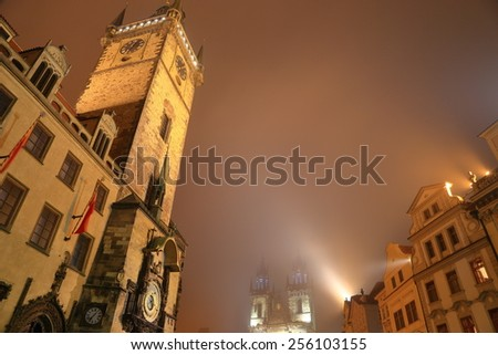 Old Town Hall tower and Astronomical Clock illuminated in foggy night, Prague old town, Czech Republic - stock photo