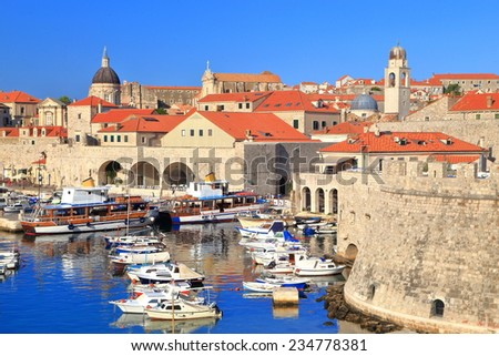 Old town harbor on the Adriatic sea coast with Venetian church and buildings, Dubrovnik, Croatia - stock photo