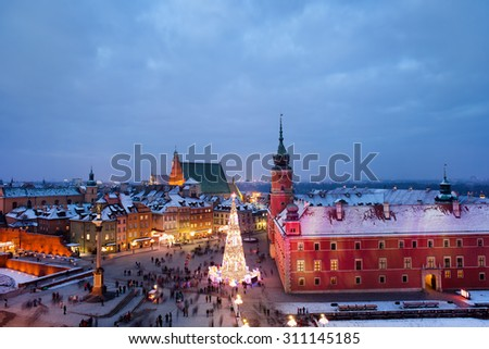 Old Town in city of Warsaw at dusk in Poland, Royal Castle, Christmas Tree on square and historic houses in winter