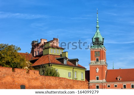Old Town in Warsaw, Poland. Clock tower of the Royal Castle, houses and fortified brick wall. - stock photo