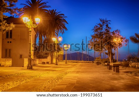 Old Town of Alghero, Sardinia Island, Italy at night. Medieval street next to city wall and marina of the city. Famous touristic destination in the Mediterranean. - stock photo