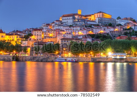 Old town of coimbra glows at night under a pretty summer sky, Portugal - stock photo