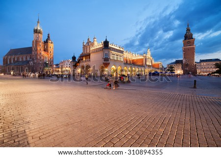 Old Town of Krakow at dusk in Poland, Main Market Square, on the left St. Mary's Church (Mariacki Church, Bazylika Mariacka) Cloth Hall (Sukiennice) in the middle, Town Hall Tower on the right.