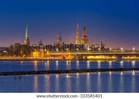 Old Town of Riga and River Daugava at night, Riga Cathedral, Saint Peter church, Cathedral Basilica of Saint James and Riga castle in the background, Latvia - stock photo