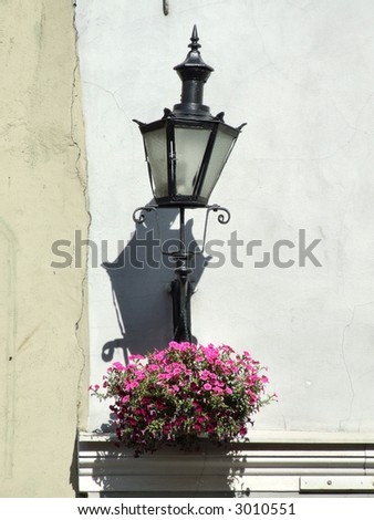 Old town scenery. Tallinn architecture. Street lamp and flowers. - stock photo