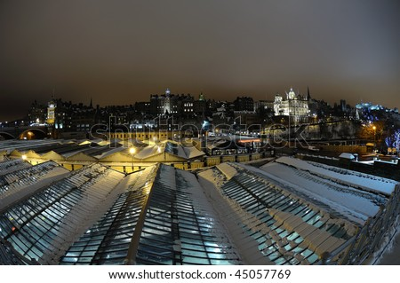 Old Town skyline, over the roof of Waverley railway station, Edinburgh, Scotland, UK, at night in winter with snow