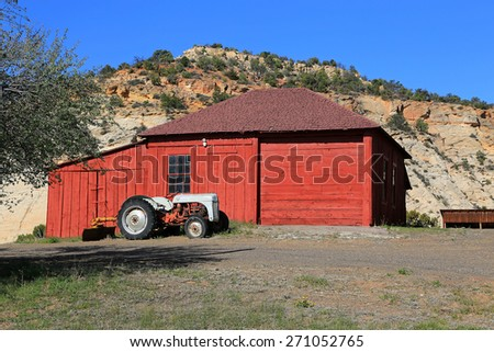Old tractor and red barn in rural Utah, USA. - stock photo