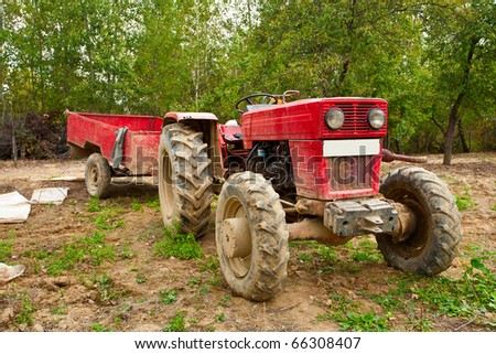 Old tractor and trailer in an orchard