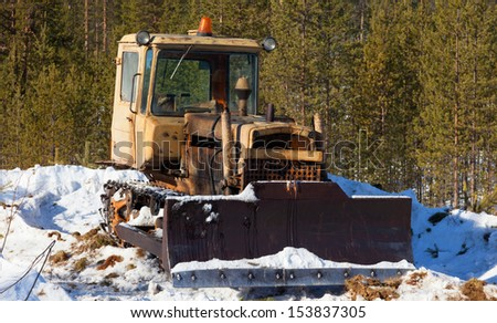 Old tractor-bulldozer cleans snow on the edge of the forest - stock photo