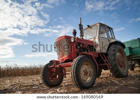 old tractor in field, cloudy sky