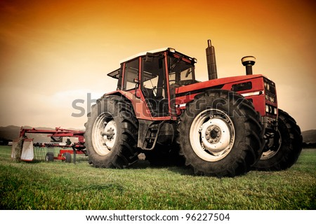 Old tractor on the grass field - stock photo