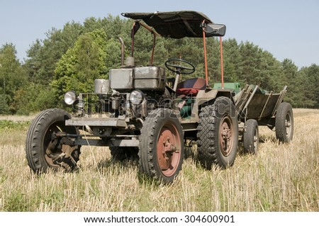 Old tractor own production with wooden trailer