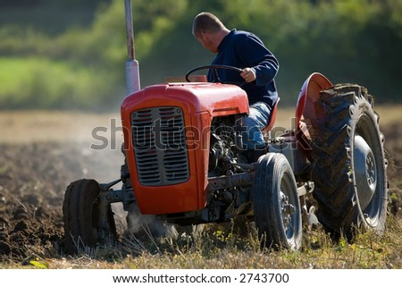 Old Tractor ploughing field - stock photo