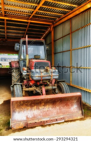 Old tractor under shed at backyard - stock photo
