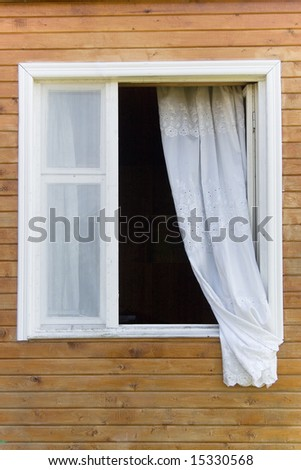 Old traditional country-style window in a wooden house (with a white curtain) - stock photo
