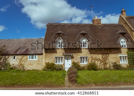 Old traditional English honey golden brown stoned cottage with colourfu flowering front garden on a summer sunny day - stock photo